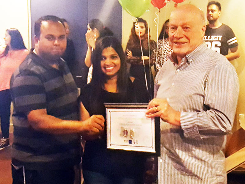 Dhiraj and Grijeshni Sharan receive their five-year Long Service Award from Richard Brodie.