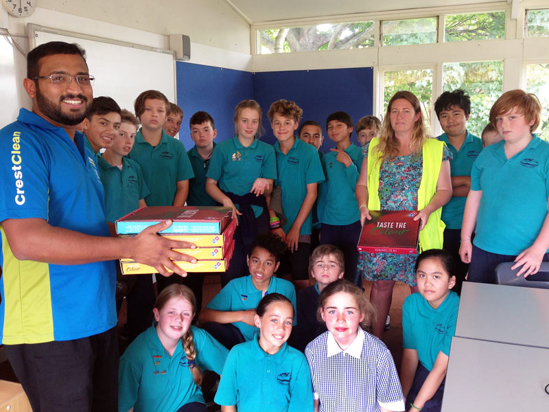 Titus Samuel hands out pizza to Room 7 pupils at Bamford School in Christchurch.
