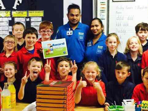 Aznayne Ali and his wife Anjeline Sahayam with kids at Milson School in Palmerston North where they handed out pizza to kids for the Cleanest Classroom Award.