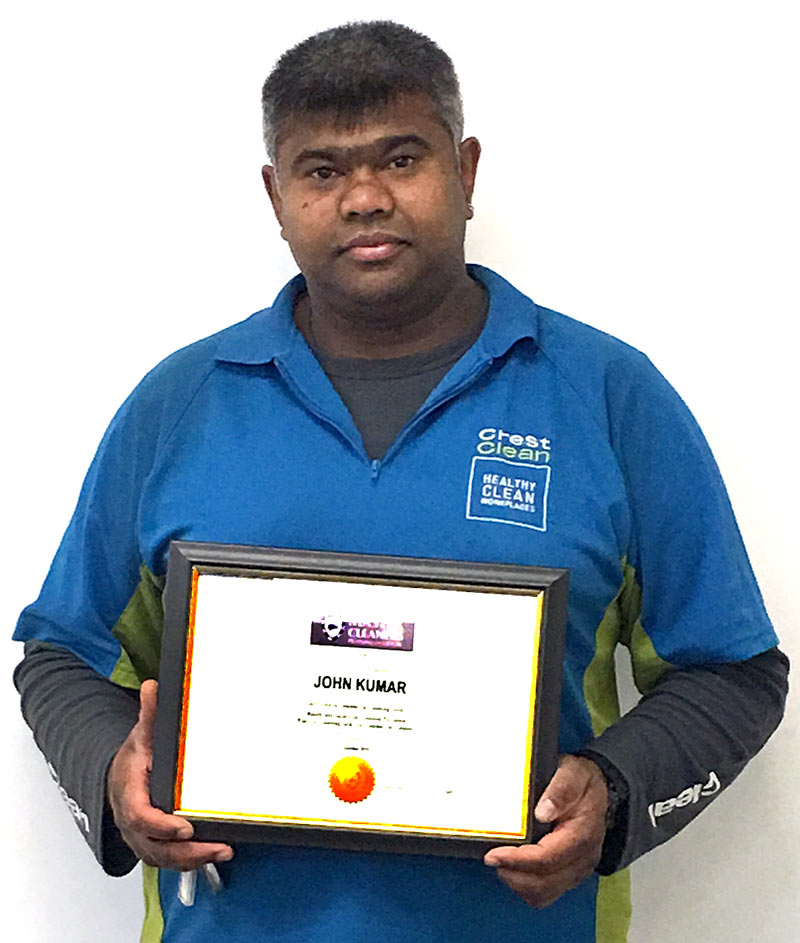 John Kumar proudly holds his award.