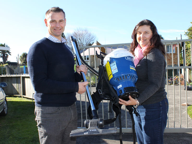 CrestClean's Jan Lichtwark presents a vacuum cleaner to Robyn Walker at Homes of Hope.