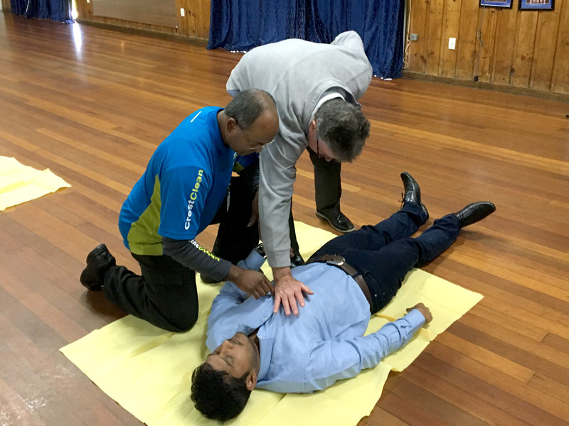 Master Cleaners Training Institute CEO Adam Hodge oversees the course as participants try CPR techniques.