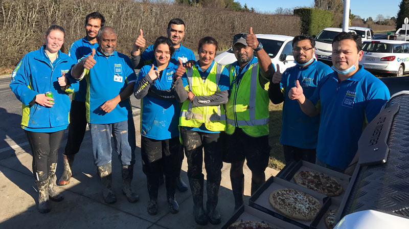 Well-earned pizza for CrestClean teams at Mosgiel pictured taking  a break from the flood clean-up work.