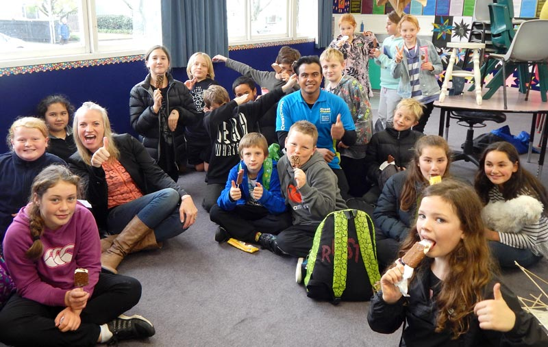 Izack Ahmed and Abby Latu give out ice-creams to students at Nelson Park Primary School after presenting the Cleanest Classroom Award to Room 17 pupils.