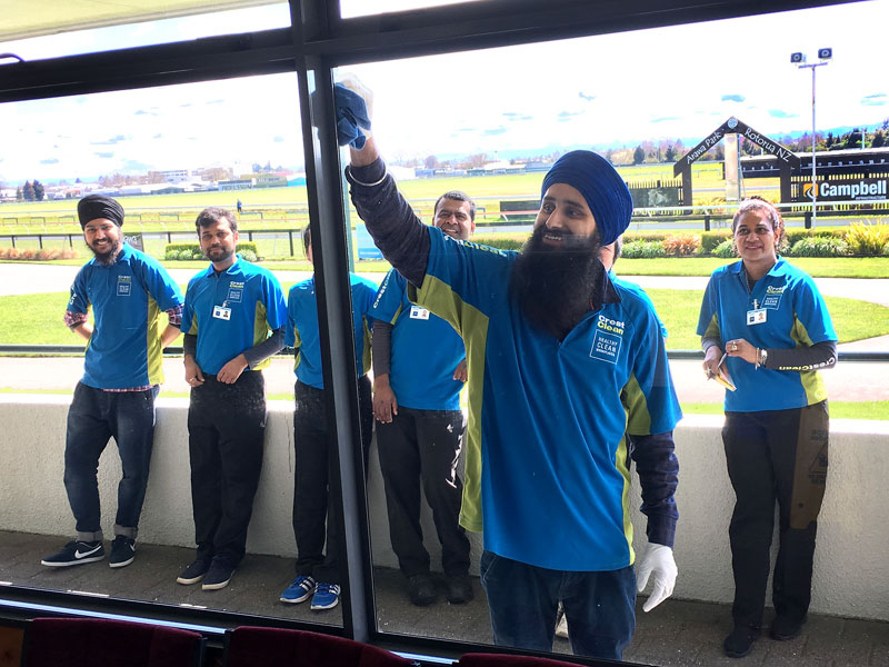 Sandeep Singh tries his hand on a large window at Rotorua Race Course during a Master Cleaners Training Institute training session.
