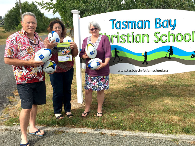 Craig Starrenburg and Judy-Anne Sunby receive the rugby balls from Barbara de Vries, CrestClean's Nelson Regional Manager.