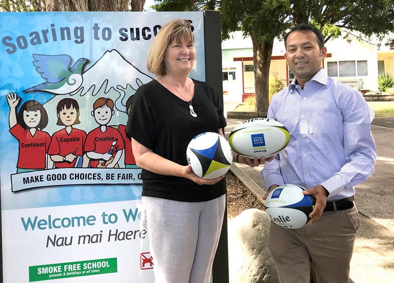 Kay Crofskey, Principal of Welbourn School, receives rugby balls from Prasun Acharya, CrestClean's Taranaki Regional Manager.