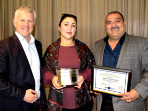 Zeynab and Khaled Khaled receive their long service award from Grant McLauchlan, CrestClean's managing director.