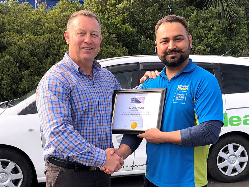 Robert Glenie presents Randeep Singh with a certificate from Master Cleaners Training Institute for an upskilling course in carpet care.