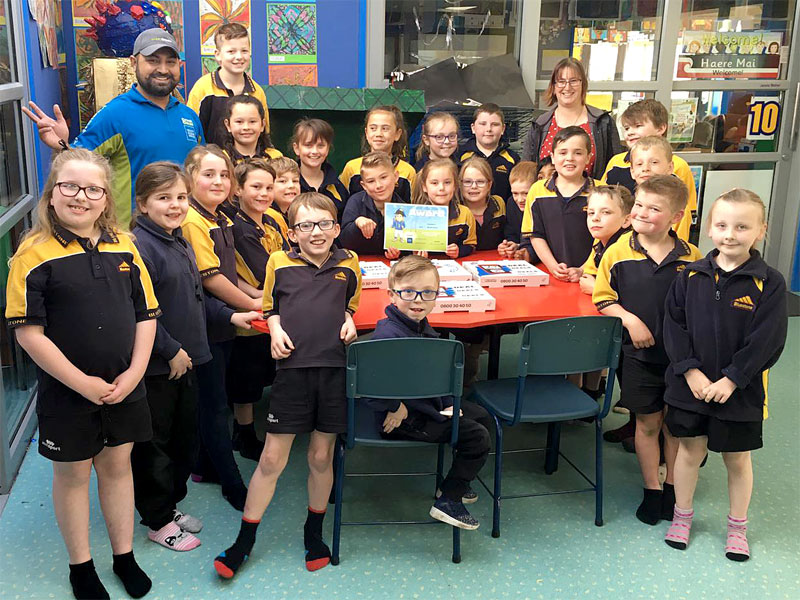 Franchise owner Randeep Singh hands out pizza to pupils at Bluestone School, Timaru for winning the Cleanest Classroom Award.