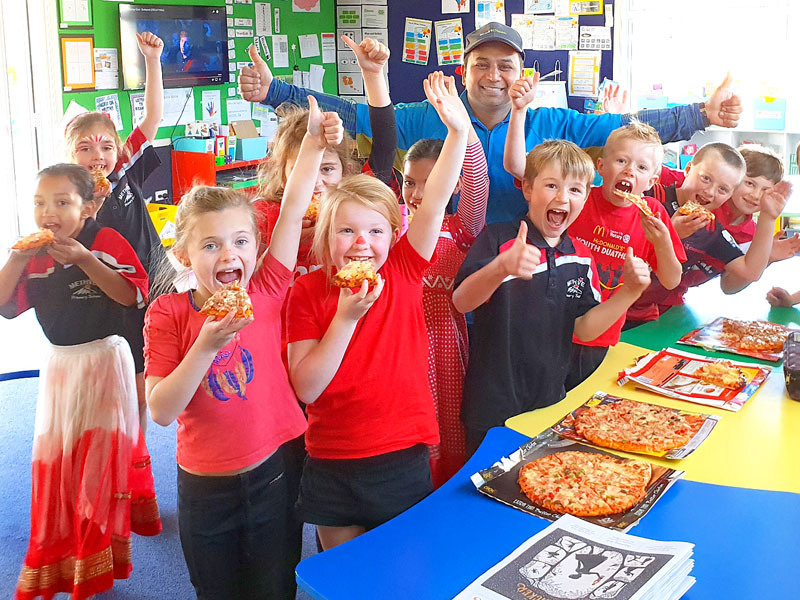 CrestClean's Sandeep Kumar hands out pizza to the winners of the Cleanest Classroom Award.