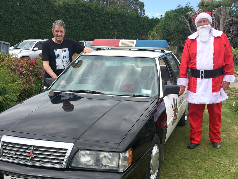 Santa arrives in spectacular style in an old traffic patrol car driven by Glenn Cockroft.