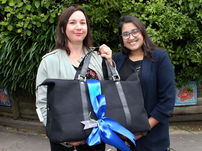 Kirsten Reid receives her Gift Saint luxury holdall from Zainab Ali, CrestClean's Wellington and Hutt Valley Regional Manager