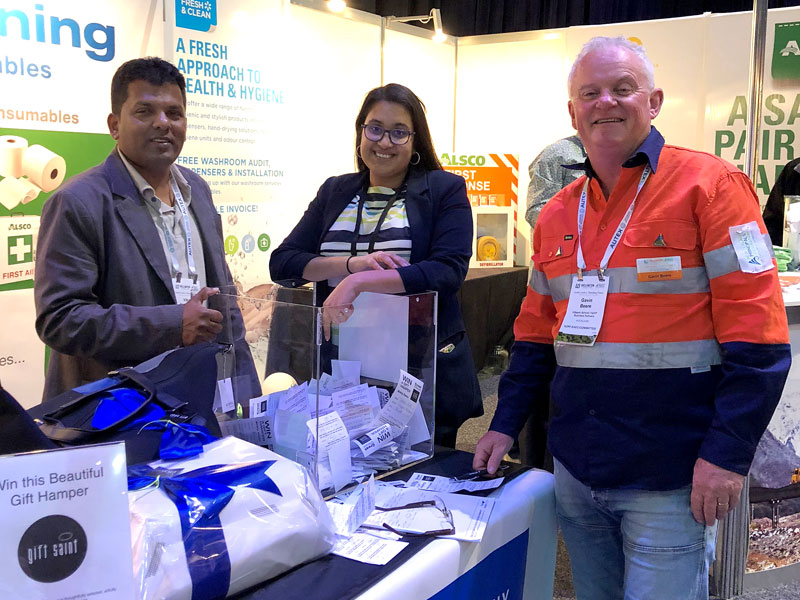 Gavin Beere makes the prize draw on the CrestClean stand. Looking on are Viky Narayan and Zainab Ali.