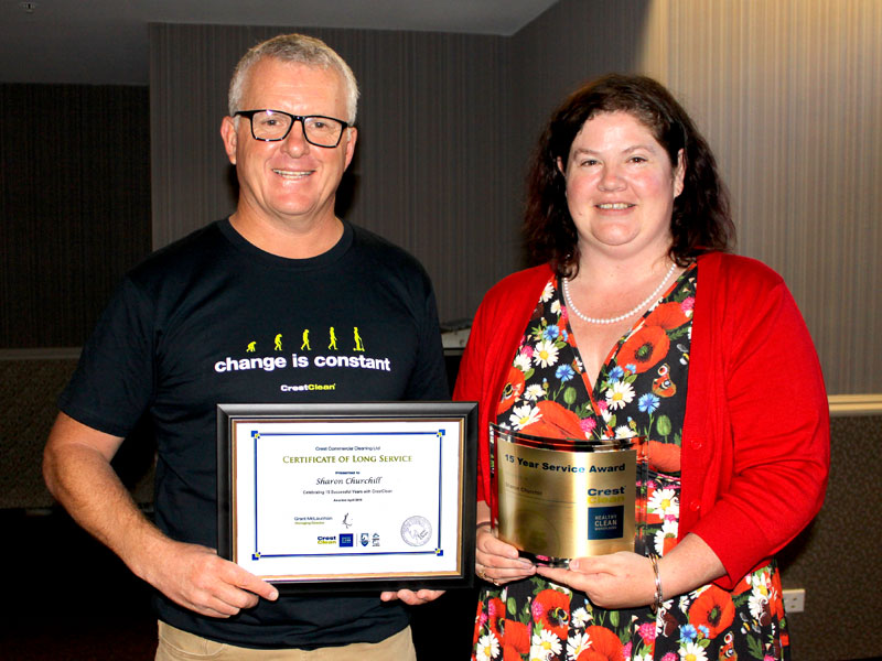 Sharon Churchill receives her long service award from Grant McLauchlan.