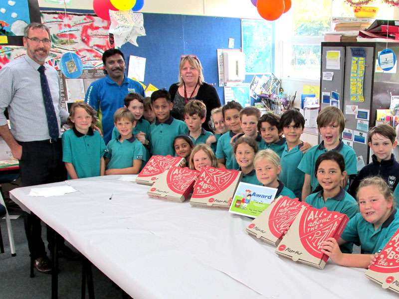 CrestClean's Jay Gounder presents pizza to children at Hastings Christian School after they won the Cleanest Classroom Award.