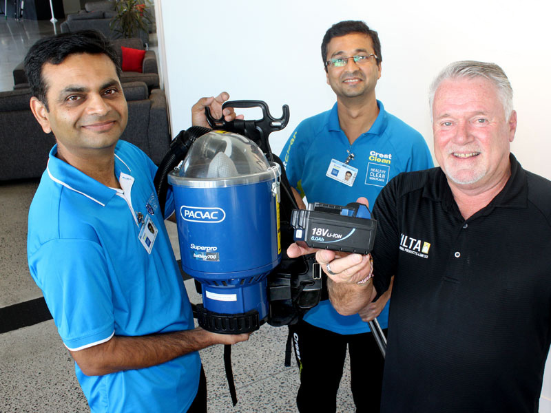 Gavin Smith shows Pinakin Patel and Chirag Kansura the battery unit from a cordless PacVac cleaner.