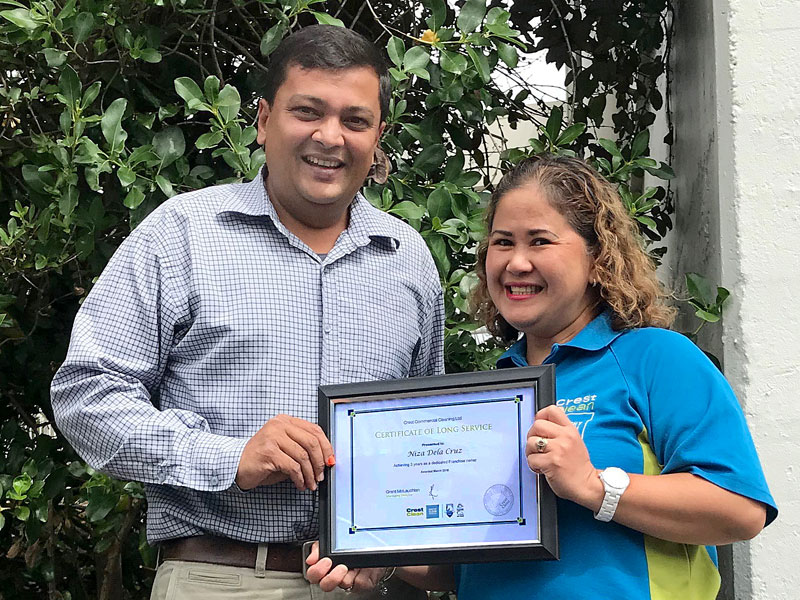 Niza Dela Cruz receives her three year Certificate of Long Service from Nivitesh Kumar, CrestClean's Waikato Regional Manager.