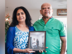 Couple holding photo of their children.