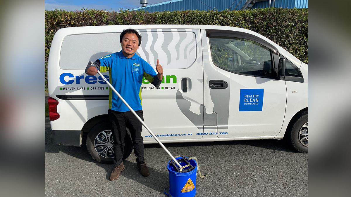 Cleaner standing by van.