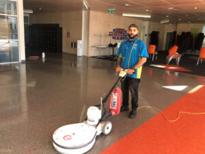 Cleaner using floor machine.